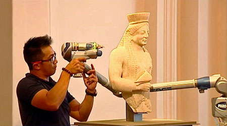 A member of Arskan scanning in 3D a statue with the 3D scanner FaroArm.