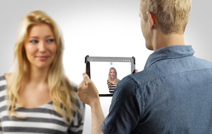 Une personne en train de se faire scanner en 3D avec une tablette équipée d'un capteur.