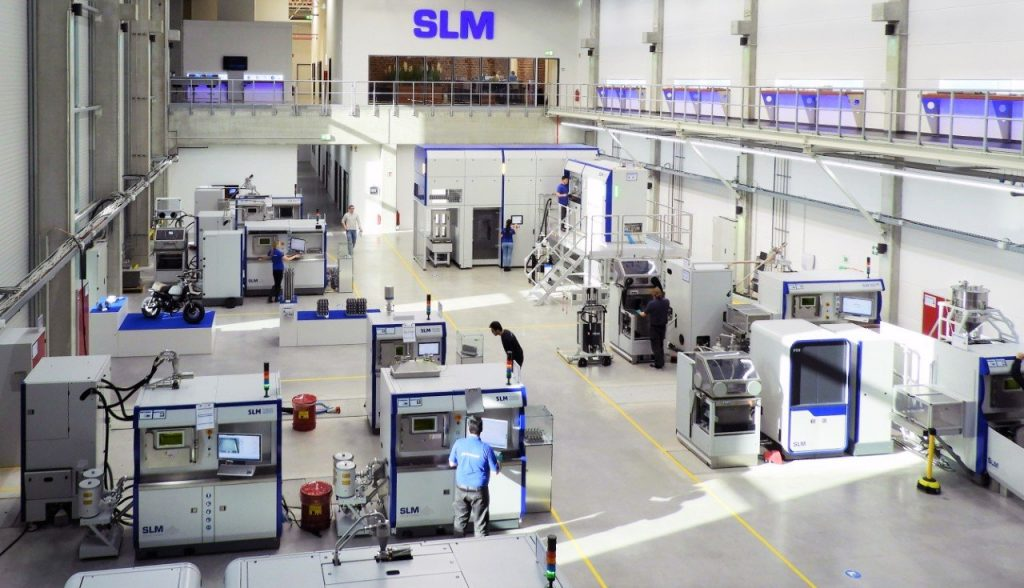 AM factory floor with metal 3D printers, powder handling stations, and other associated systems from SLM Solutions.